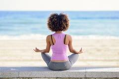 Murzynka, afro fryzura, robi joga w plaży Obraz Stock