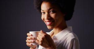 Murzynka pije gorącą kawę i ono uśmiecha się z afro w studiu Zdjęcia Royalty Free