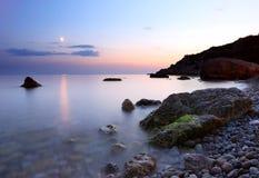 Musardez le chemin au-dessus de la mer de nuit après le coucher du soleil Photos stock