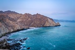 Muscat Beach Landscape. Beautiful bird`s eye view of barren, pointy mountains and turquoise sea water in Oman stock images