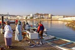 MUSCAT, OMÃ - 11 DE FEVEREIRO DE 2012: O pescador nos peixes de Muttrah entra o amanhecer com corniche de Muttrah no fundo Fotografia de Stock