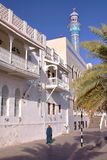 MUSCAT, OMAN - FEBRUARY 10, 2012: An Omani man walking along Sur Al Lewatia Mosque in Muttrah. An Omani man walking along Sur Al Lewatia Mosque in Muttrah Royalty Free Stock Photography