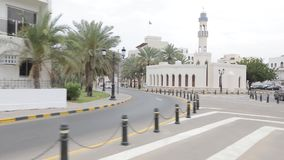 Traffic at corniche in Muscat, Kingdom of Oman. Ð¡ity road along the palm trees. Muscat, Oman, - February 2019. Traffic at the corniche in Muscat. The city stock video footage