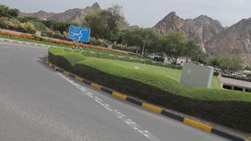 Traffic at corniche in Muscat, Kingdom of Oman. Ð¡ity road along the mountains. Muscat, Oman, - February 2019. Traffic at the corniche in Muscat. The city road stock footage