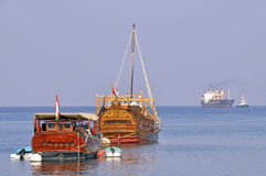 Muscat Oman harbour with Dhows and modern freighter Stock Photography