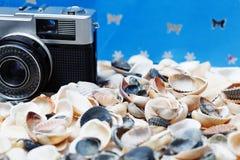 Muschel und Kamera auf dem Strand Lizenzfreies Stockbild