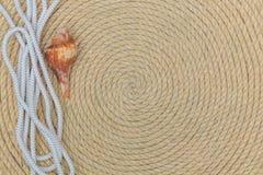 Muschel und Marinenetz liegen auf dem Hintergrund, der vom Seil gemacht wird Lizenzfreies Stockfoto