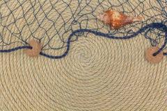 Muschel und Marinenetz liegen auf dem Hintergrund, der vom Seil gemacht wird Lizenzfreie Stockfotografie