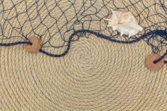 Muschel und Marinenetz liegen auf dem Hintergrund, der vom Seil gemacht wird Stockbild