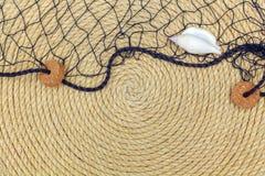 Muschel und Marinenetz liegen auf dem Hintergrund, der vom Seil gemacht wird Lizenzfreie Stockbilder