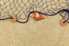 Muschel und Marinenetz liegen auf dem Hintergrund, der vom Seil gemacht wird Lizenzfreie Stockfotos