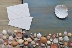 Muscheln auf cyan-blauem Holz mit leerem Buchstaben stockfoto