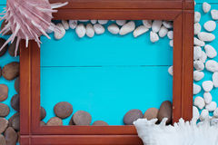 Muscheln und Kiesel mit Holzrahmen auf hölzernem Hintergrund Lizenzfreie Stockbilder