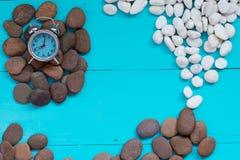 Muscheln und Kiesel mit Wecker auf hölzernem Hintergrund Stockfotografie