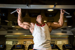 Muscle athlete man in gym making elevations. royalty free stock image