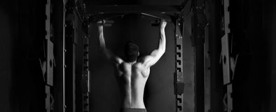Muscle athlete man in gym making elevations Stock Photos