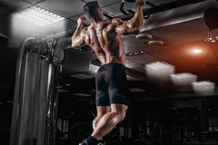 Muscle athlete man in gym making pull up. Muscle athlete man in gym making elevations. Bodybuilder training pull up in gym royalty free stock photos