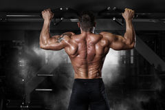 Muscle athlete man in gym making pull up. Muscle athlete man in gym making elevations. Bodybuilder training pull up in gym Royalty Free Stock Image