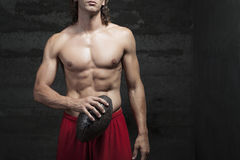Muscle bare chested. Bare chested muscle man is holding football ball in hand Stock Photo