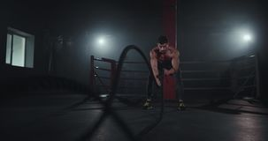 Muscle body man practicing cross fit exercises using a ropes he get concentrated in what he does.  stock video