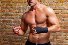 Muscle boxer shaped man with fist bandage. In red and black on brickwall Stock Photo