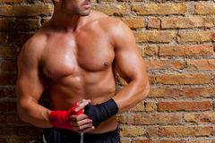 Muscle boxer shaped man with fist bandage. In red and black on brickwall Royalty Free Stock Image
