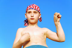Muscle boy. In motion on blue sky background Stock Photography
