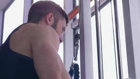 Muscle building, sports male doing power workout on traction simulator while working on body at gym at sports center stock video footage