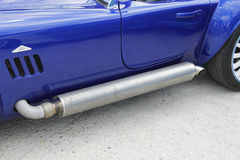 Muscle car exhaust pipe protection grille on side. Exhaust pipe metallic protection grille of a blue American muscle car. Big ventilation grille on the side Stock Photo