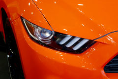 Muscle car headlight orange body paint. Modern xenon an LED headlight of an orange muscle car Stock Photo