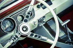 Muscle car interior. Retro toned American muscle car dashboard and steering wheel Royalty Free Stock Image