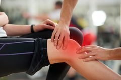 Muscle cramp during workout. Male hands helping relieve pain in female injured leg. Sport accident concept stock images