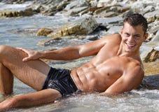 Muscle den reizvollen blanken Mann des nassen Lächelns, der im Meerwasser liegt Lizenzfreies Stockfoto