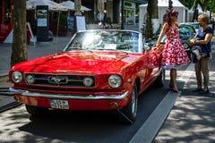 Muscle el descapotable de Ford Mustang del coche, 1965 y a una mujer en un vestido de 60 ` s Fotos de archivo libres de regalías