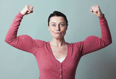 Muscle and female independence metaphor for fun 40s woman Royalty Free Stock Photography
