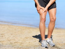 Muscle injury. Runner man with sprain thigh muscle. Athlete in sports shorts clutching his thigh muscles after pulling or straining them while jogging on the stock images