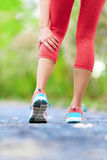 Muscle injury - woman running clutching calf muscle Royalty Free Stock Photo