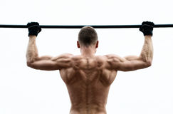 Muscle l'homme faisant le pull-up sur la barre horizontale contre le ciel Photographie stock
