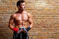 Muscle l'uomo del pugile con la fasciatura ed i pesi del pugno Immagine Stock