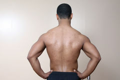 Muscle man. Young male flexing back and arm muscles Stock Photography