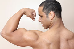 Muscle man. Young male flexing back and arm muscles Royalty Free Stock Images