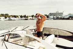 Muscle man on a boat. Muscle body builder man on a boat Royalty Free Stock Photos