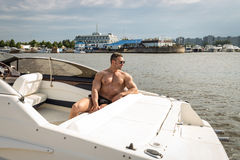 Muscle man on a boat. Summer stock photos