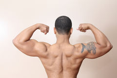 Muscle man, both arms flexed. Young male flexing back and arm muscles Royalty Free Stock Photos