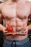 Muscle man choice between apple and pills Royalty Free Stock Image