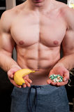 Muscle man choice between banana and pills Stock Photo