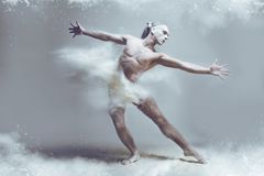 Muscle man dancer in dust / fog. Dancing in flour concept. Naked muscle man dancer in dust / fog. Guy wearing white shorts making dance element stretching his royalty free stock image