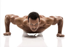 Muscle man. Dmaking push ups in studio, isolated over a white background Stock Photo