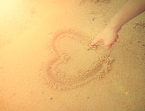 Muscle man draw heart on sand. International sun light and vinta Stock Photography
