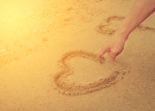 Muscle man draw heart on sand. International sun light and vinta Stock Image